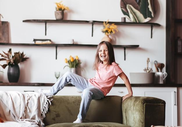 リビングルームのソファで元気に遊んでいる小さな幸せな女の子