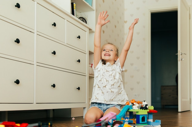 Little happy girl playing with colorful toy blocks. educational and creative toys and games for young children. playtime and mess in kid's room