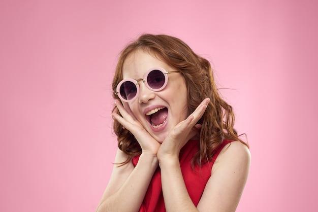 Маленькая счастливая девушка позирует в очках, красивый улыбающийся ребенок