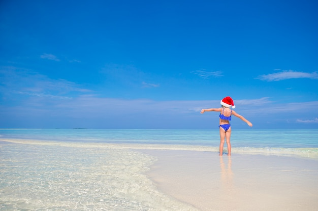 Little happy girl in santa hat during beach vacation on maldives