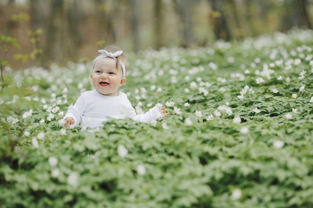 Little happy girl sits among the flowers in the woods