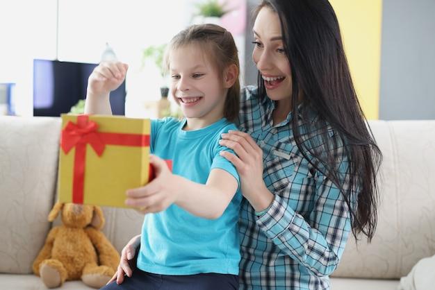 Маленькая счастливая девочка сидит на коленях у матери и открывает дома подарочную коробку