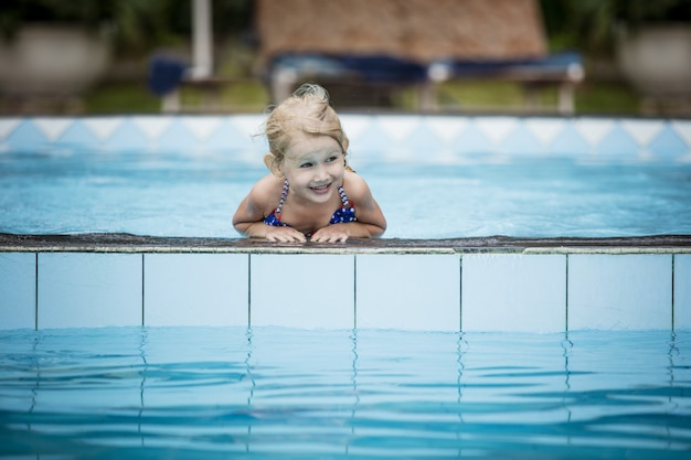 아름답고 행복한 야외 수영장에서 웃고 수영하는 어린 행복한 소녀
