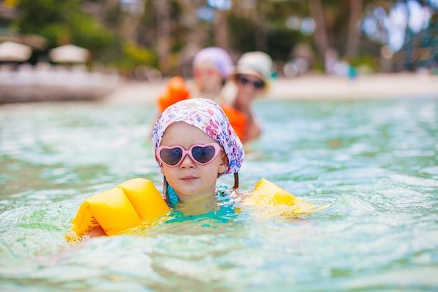 Little happy girl splashing in clear turquiose water