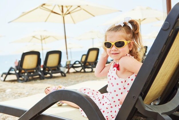 Little happy girl on the sunbeds by the sea