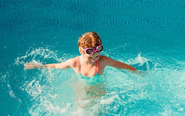 작은 행복 소녀는 수영장에서 수영. 여름 방학. 수영복과 수영 안경에 소녀입니다.