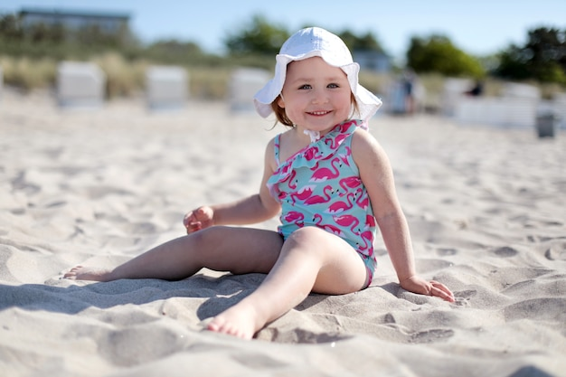 Little happy girl on white sand beach enjoying summer and vacation.