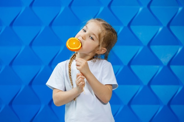 오렌지를 손에 들고 행복한 어린 소녀는 흰색 티셔츠를 입은 카메라를 쳐다보고 파란색 배경에 격리되어 공간을 복사합니다.