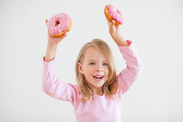 Маленькая счастливая девочка со светлыми волосами играет и дегустирует пончики с розовой глазурью на праздновании хануки