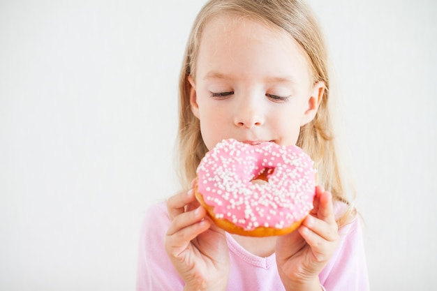Little happy girl with blond hair playing and tasting donuts with pink icing at hanukkah celebration