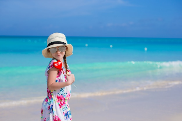Little happy girl with red heart in hands on a tropical beach