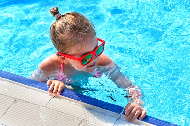サングラスをかけた幸せな少女が夏にプールで泳ぐ