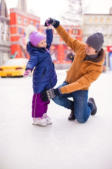 Little happy girl with young father have fun on skating rink