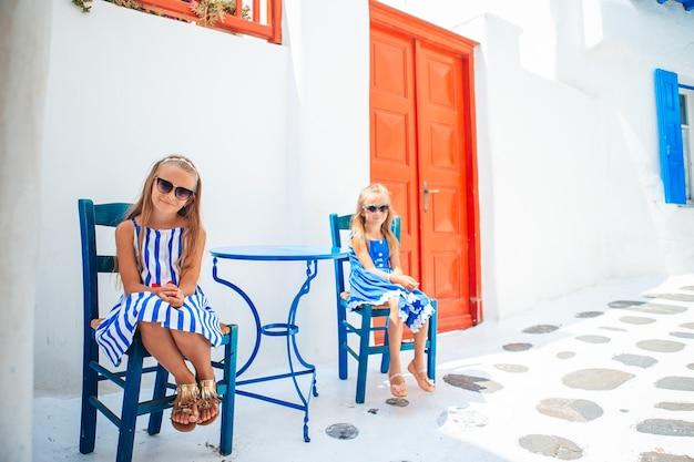 Little happy girls in dresses at street of typical greek traditional village on mykonos island, in greece