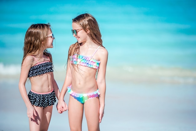 Little happy girls having a lot of fun together on the beach