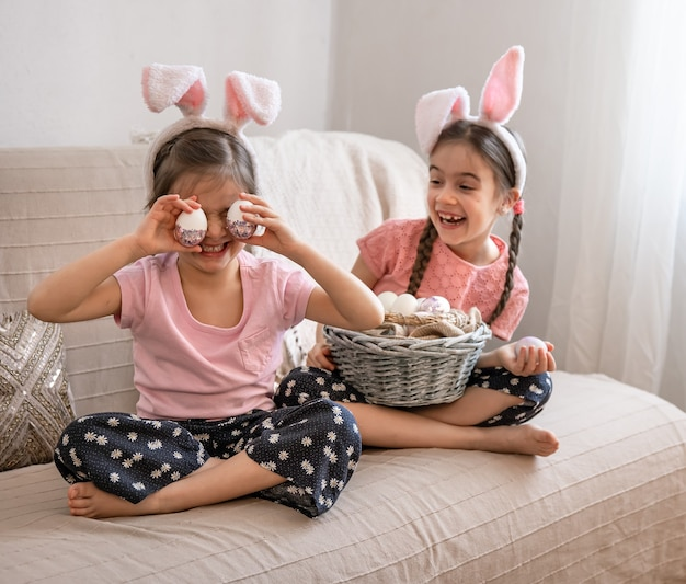 Маленькие счастливые сестры с кроличьими ушками позируют с корзиной пасхальных яиц