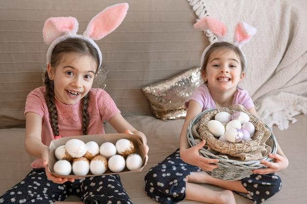 Маленькие счастливые сестры с кроличьими ушками, с пасхальными яйцами