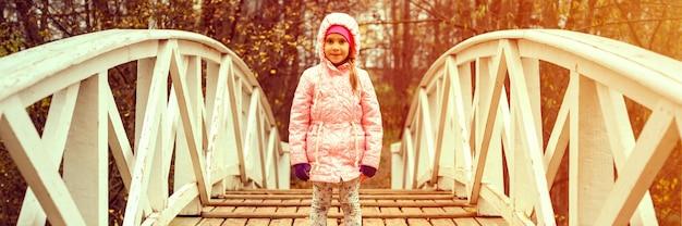 Маленькая счастливая шестилетняя девочка в осенней одежде стоит на горбатом деревянном мосту в осеннем парке. баннер. вспышка