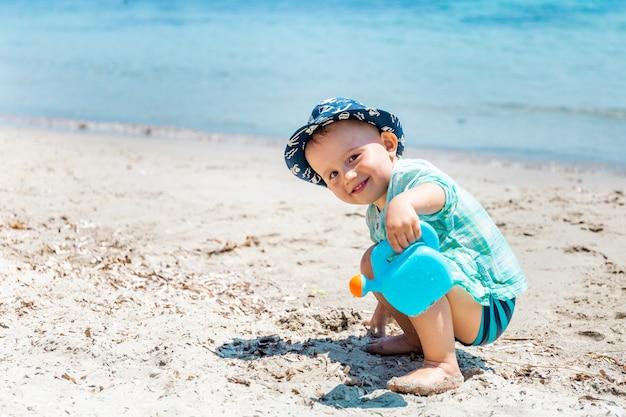작은 행복한 어린 소년이 해변에서 모래와 물이 있는 물뿌리개 장난감을 가지고 놀고 있습니다.