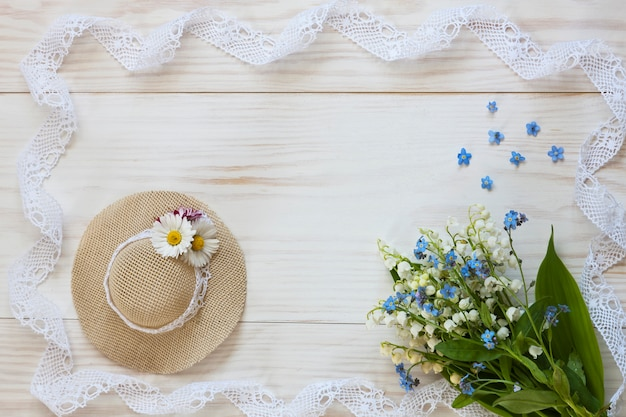 Little hat, lilies of the valley, and lace on a white wooden background.