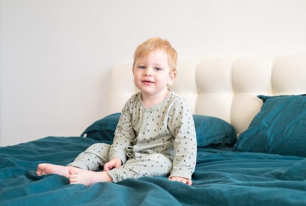 自宅のベッドに座って笑っている緑のパジャマを着た小さな健康な幼児の男の子。
