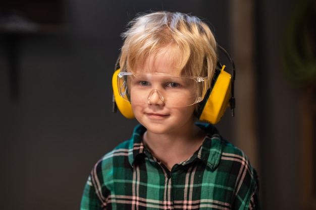 Little helper of a carpenter or builder, blond hair in a shirt, protective glasses and headphones, close-up portrait.