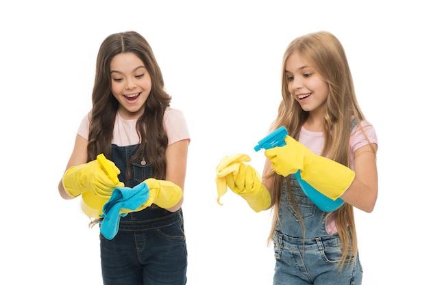 リトルヘルパー。ミスト噴霧器で周りを掃除している女の子のかわいい子供たち。清潔に保ってください。姉妹のライバル。誰が上手くいったか。黄色のゴム製保護手袋を着用した女の子は、掃除の準備ができています。家事。