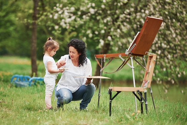 Little helper. teaching granddaughter how to paint. in the natural parkland