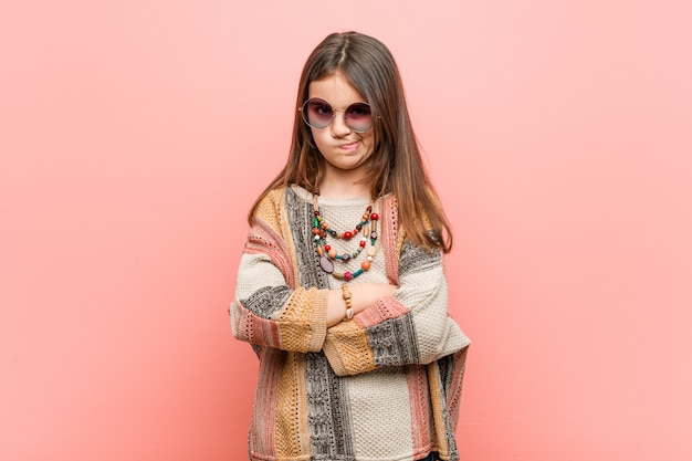 Little hippie girl frowning face in displeasure, keeps arms folded.