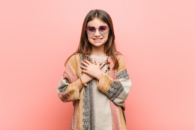 Little hippie girl has friendly expression, pressing palm to chest.