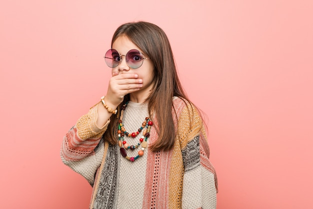 Little hippie girl thoughtful looking to a copy space covering mouth with hand.