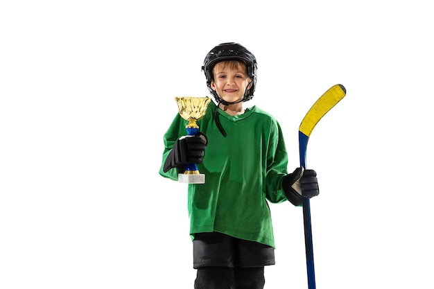 Little hockey player with the stick on ice court and white background. sportsboy wearing equipment and helmet training.