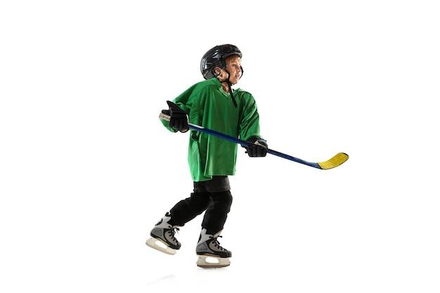 Piccolo giocatore di hockey con il bastone sul campo da ghiaccio, sfondo bianco studio. sportsboy che indossa attrezzatura e casco, pratica, formazione. concetto di sport, stile di vita sano, movimento, movimento, azione.