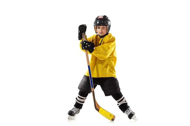 Piccolo giocatore di hockey con il bastone sul campo da ghiaccio e la parete bianca dello studio