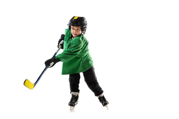 Piccolo giocatore di hockey con il bastone sul campo da ghiaccio, muro bianco. sportsboy che indossa attrezzatura e casco, pratica, allenamento. concetto di sport, stile di vita sano, movimento, movimento, azione.