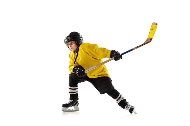 Piccolo giocatore di hockey con il bastone sul campo da ghiaccio e muro bianco