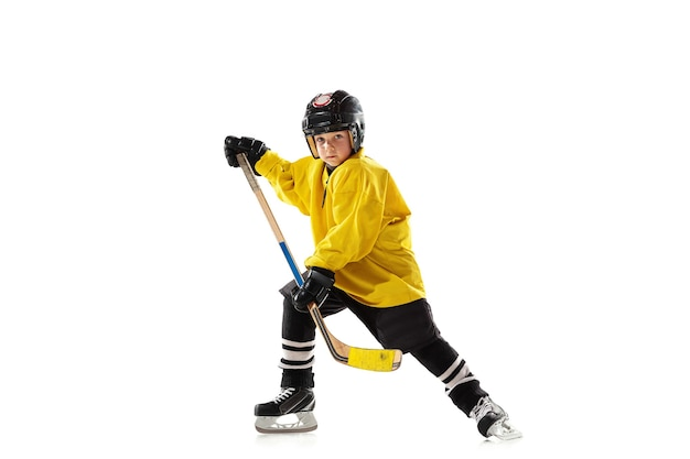 Little hockey player with the stick on ice court and white wall
