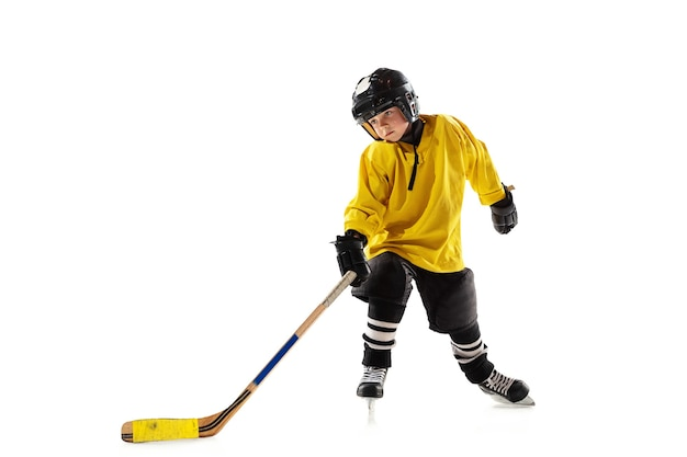 Little hockey player with the stick on ice court and white