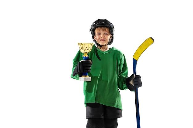 アイスコートと白い背景の上の棒を持つ小さなホッケー選手。装備とヘルメットのトレーニングを身に着けているスポーツボーイ。