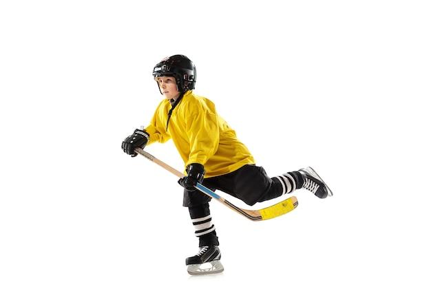 Маленький хоккеист с клюшкой на ледовой площадке и белый
