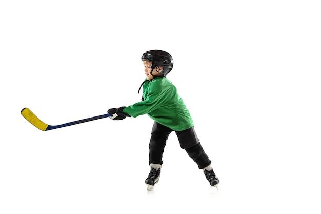 アイスコート、白い背景の上の棒を持つ小さなホッケー選手。装備とヘルメットを着用し、練習、トレーニングをしているスポーツボーイ。