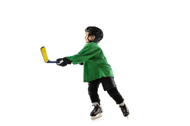 アイス コート、白いスタジオの背景にスティックを持つ小さなホッケー選手。スポーツ少年が装備とヘルメットをかぶり、練習、トレーニング。スポーツのコンセプト、健康的なライフスタイル、動き、動き、行動。