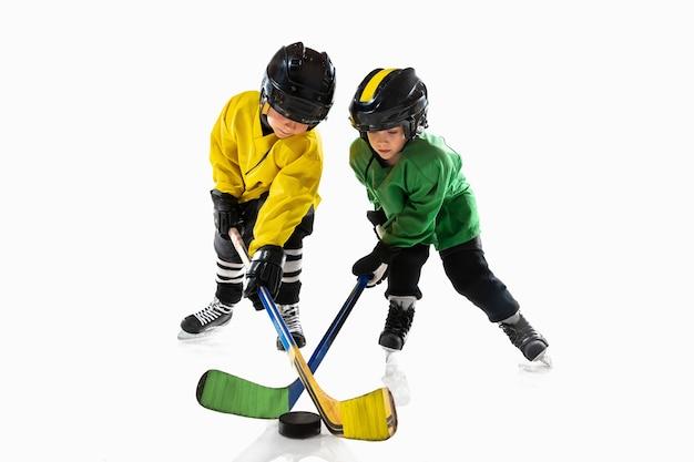 Piccoli giocatori di hockey con i bastoni sul campo da ghiaccio e sfondo bianco.