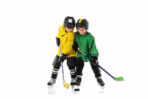 Piccoli giocatori di hockey con i bastoni sul campo da ghiaccio e la parete bianca dello studio