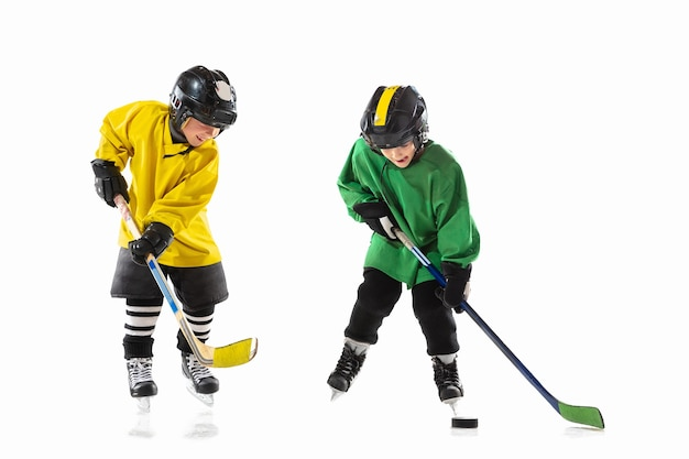 아이스 코트와 흰 벽에 막대기와 작은 하키 선수. sportsboys 착용 장비 및 헬멧 연습. 스포츠, 건강한 라이프 스타일, 운동, 운동, 행동의 개념.