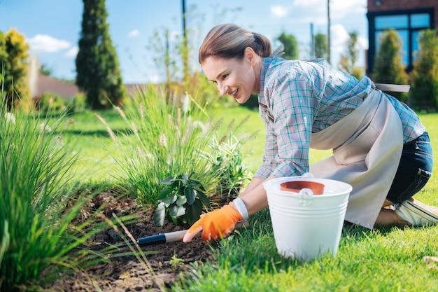 Little hoe. beaming gardener wearing bright orange gloves holding little hoe in her hands while grubbing weeds up