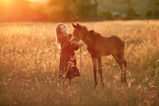 草原の上を歩く赤い髪の少女と小さな馬の子馬