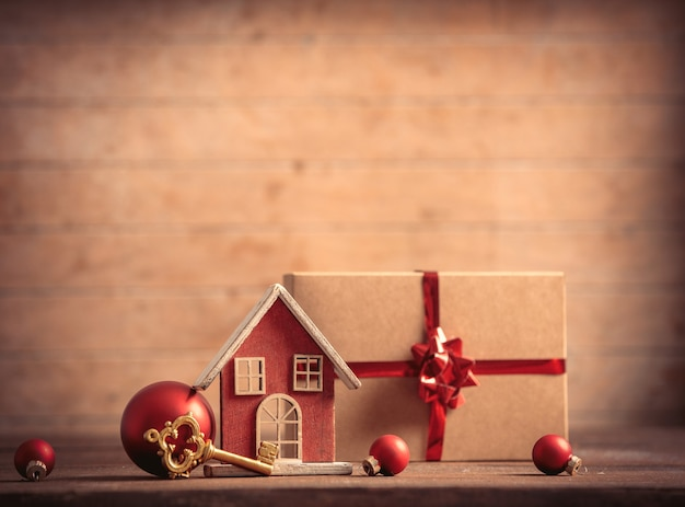 Little house and key with christmas box on wooden table