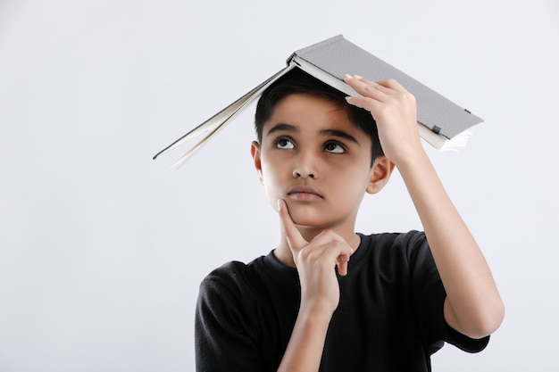 Little indian / asian boy with book on head and thinking seriously