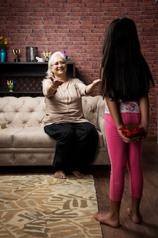 Маленькая индийская азиатка прячет подарок-сюрприз за спиной, а бабушка взволнована и сидит дома на диване или диване